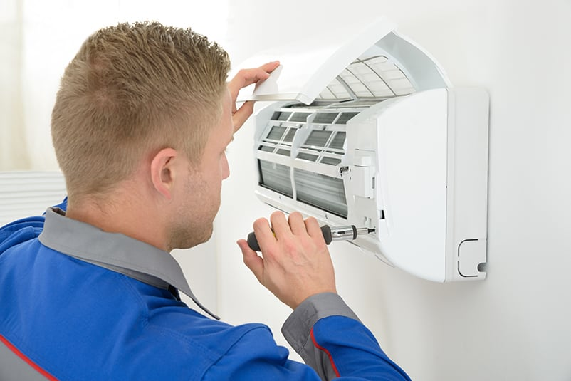 A man fixing an air conditioning unit. HVAC Jobs near me