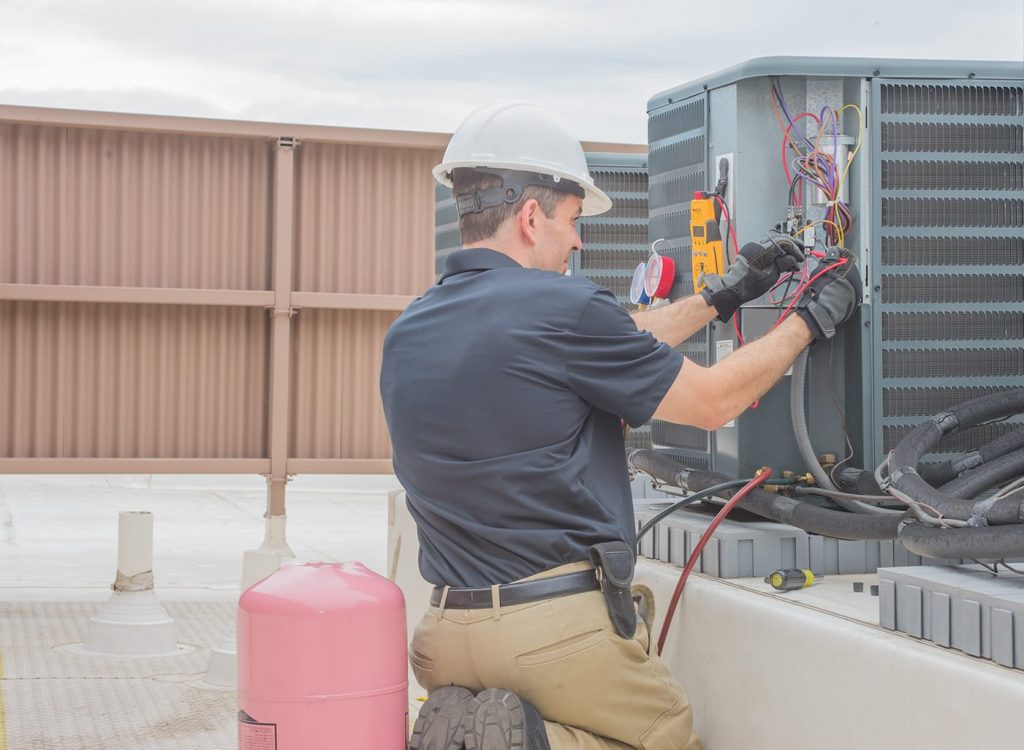 A commercial hvac professional working on a rooftop hvac unit.