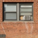 A window AC Unit inside the window of a brick building. Depending on your home or apartment, you should still know the pros and cons of deciding between central air vs window unit.