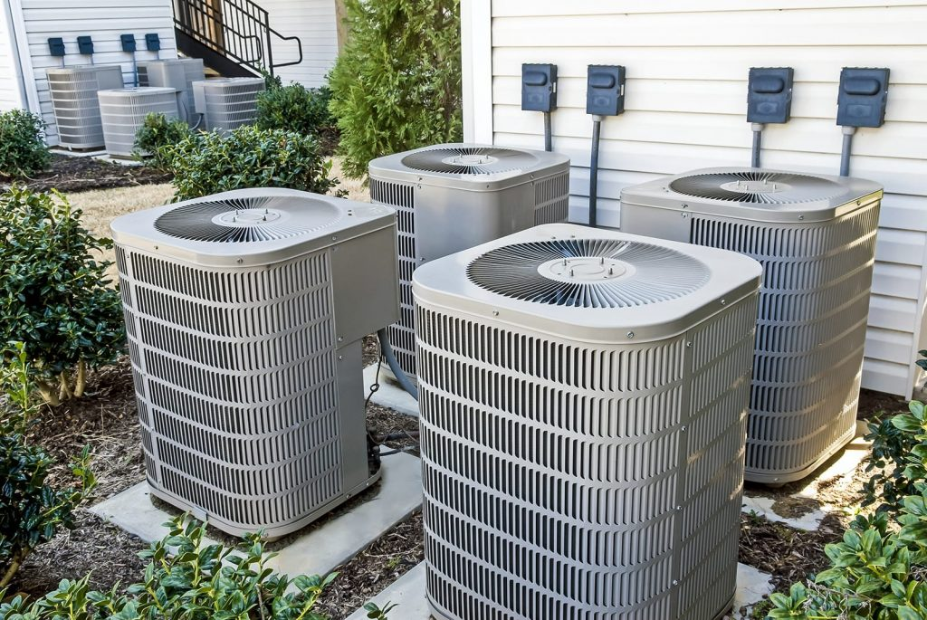 Learn how to avoid HVAC problems as winter turns to spring. Four AC units outside an apartment complex.