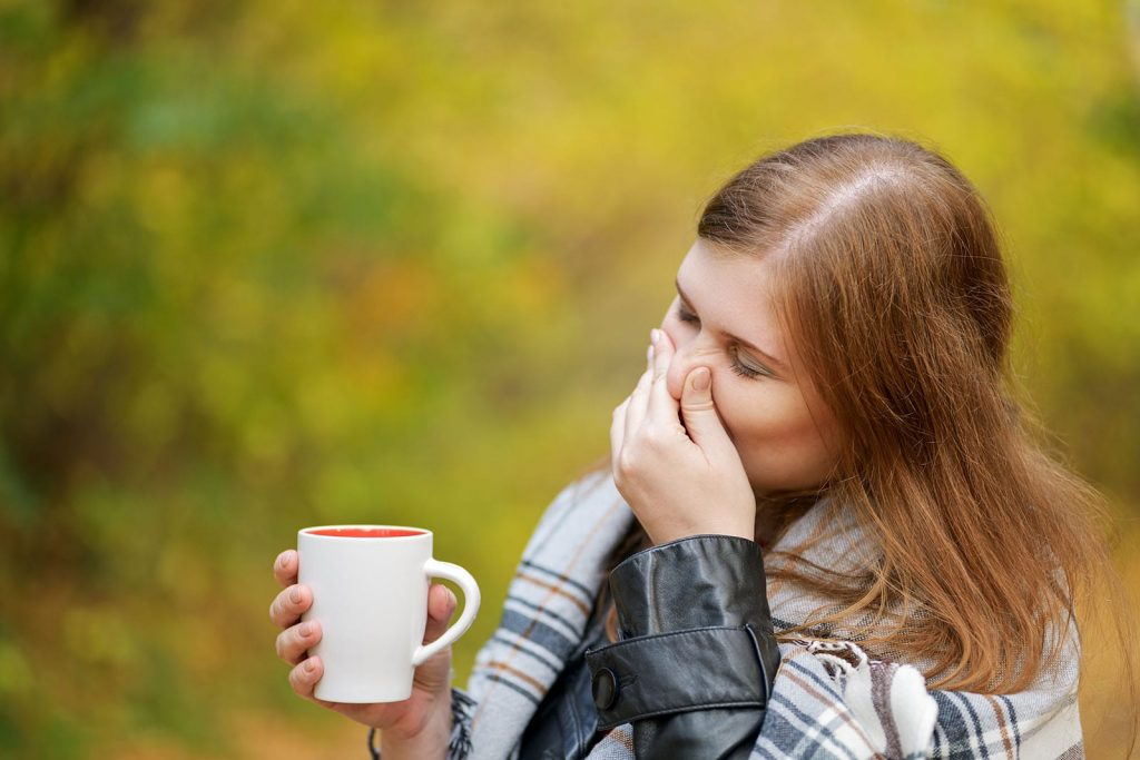 Fall allergens and airways don't always mix well. A woman plugs her nose while drinking a cup of coffee outside during autumn.