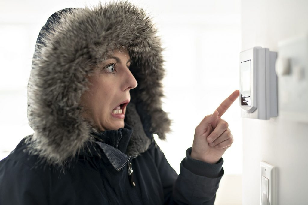 Some furnace tune-ups may be in need if cold air is coming out that's not supposed to. A freezing woman in a parka yells at her thermostat