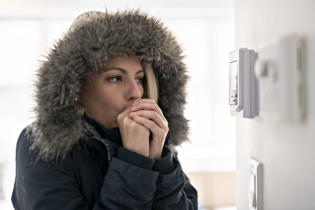 A programmable thermostat can keep you from checking the house's temperature. A freezing cold woman in a parka check her thermostat.