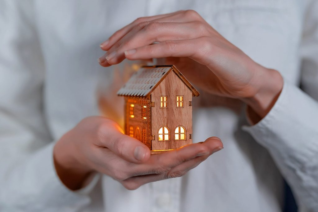 Proper winter insulation will keep your home coxy no matter the conditions outside. Hands holding a small wooden house with the lights on.