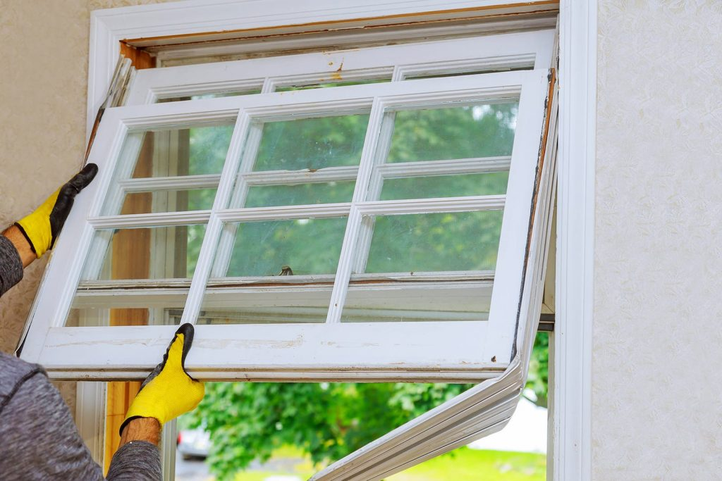 Replacing a window sill with energy efficient windows.