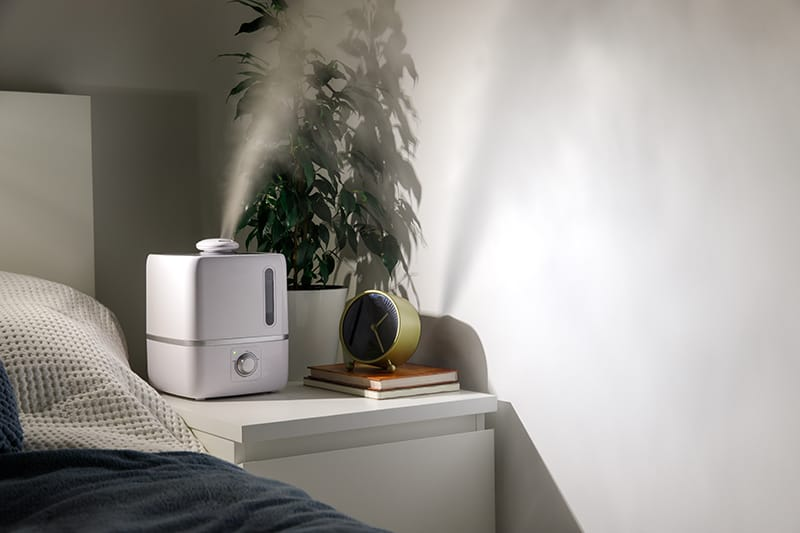 A small space humidifier sits on a nightstand pulsing water mist into the air.