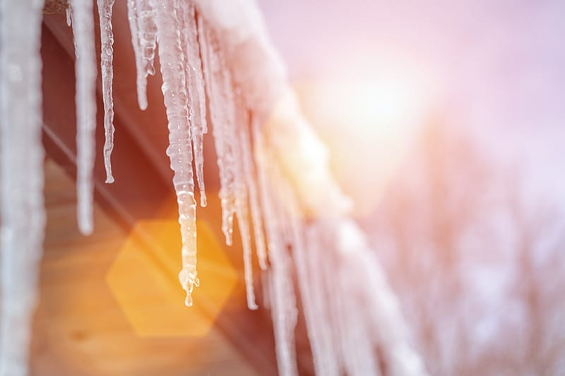 The sun melting icicles with a ray of light. Follow Sharon's spring HVAC maintenance tips for dealing with sudden snow melting and when to turn on the AC.