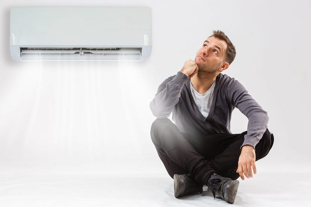A man sitting down, looking at his interior wall-mounted ac unit, wondering why his air conditioner always on.