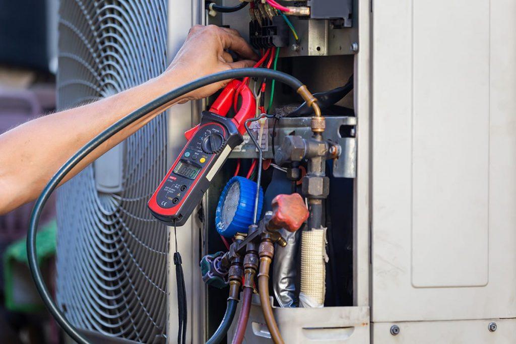 A technician conducting regular hvac maintenance on an exterior air conditioner.