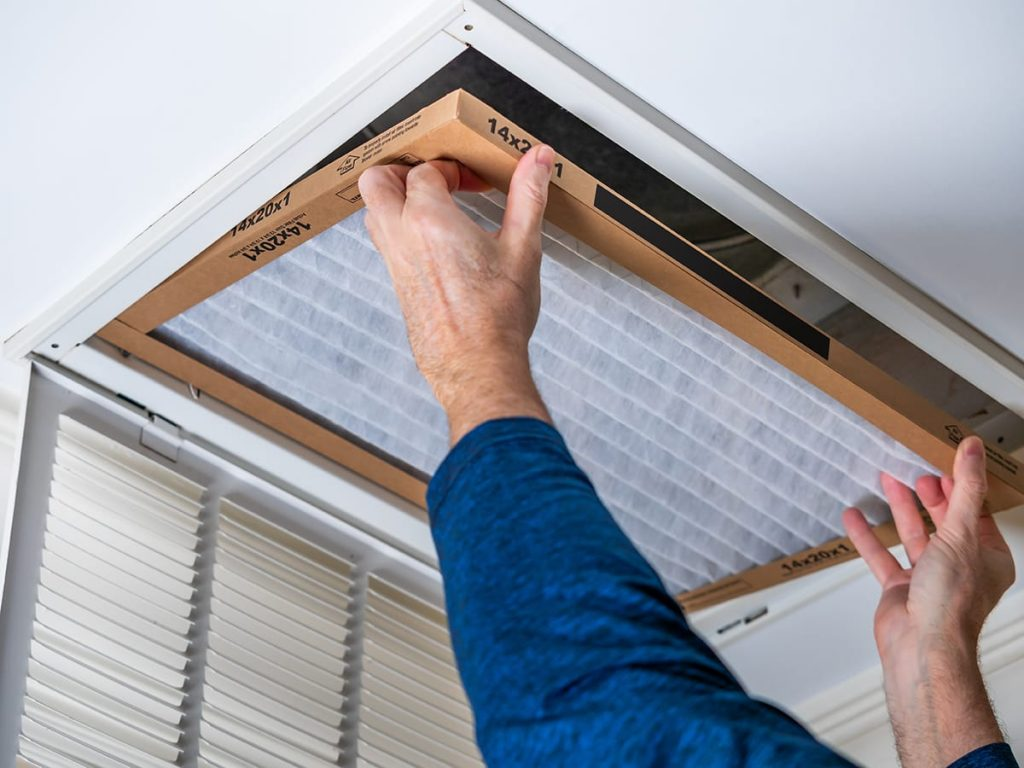 An HVAC technician replacing an air filter on a ceiling duct. how often to replace air filter? At least every quarter.