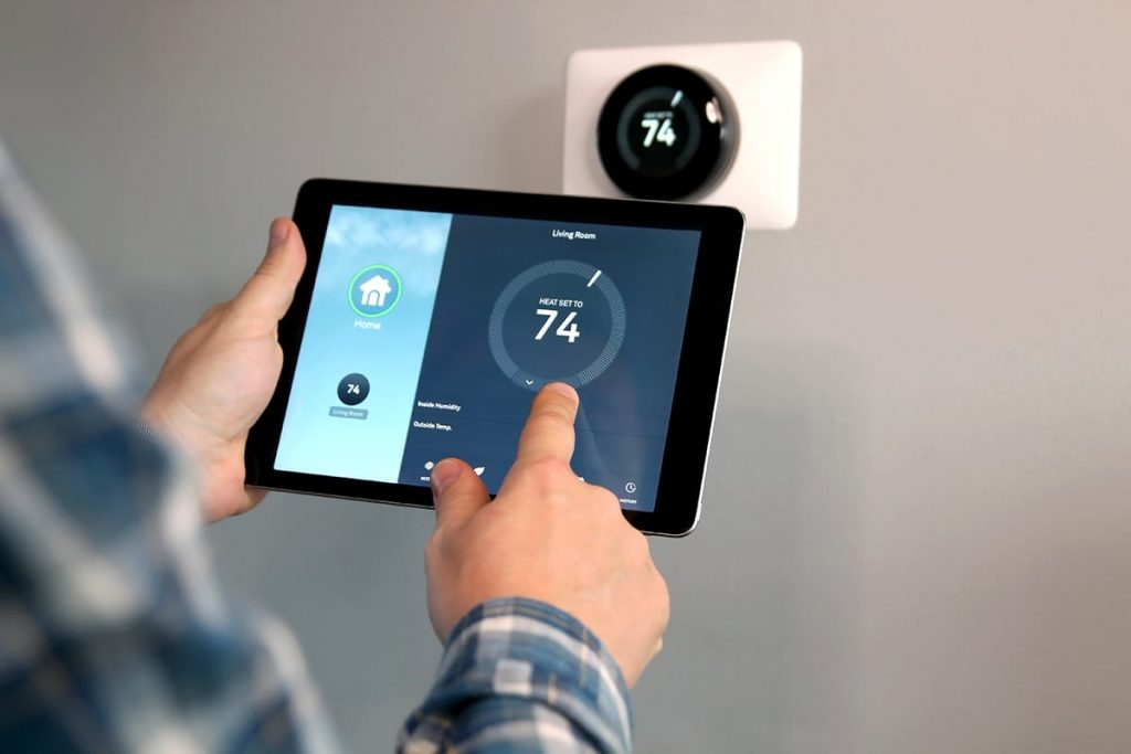 A man uses an ipad to set the temperature to 74 degrees on his smart thermostat.